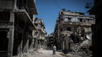 A Syrian refugee walks among severely damaged buildings in downtown Homs, Syria, on June 3, 2014.