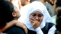 A Muslim girl supports her Christian friend after her brother was killed during the battles of Maspero, Egypt, 2011