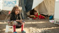 A young girl sits outside a UNHCR tent in war-ravaged Syria