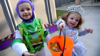 Two children show off their Halloween candy