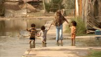 Iraqi family wades through water