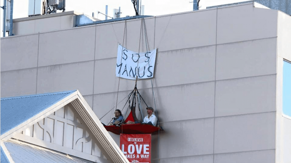 Jarrod McKenna and Delroy Bergsma are suspended four storeys up, protesting what is happening on Manus Island