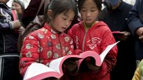 Two little girls outside a rural church in Henan Province reading the Bibles they have just received during a visit to their church