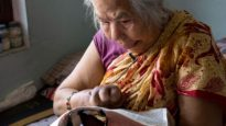 A leprosy victim in Nepal reads the Bible.