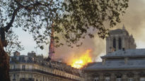 Notre Dame on fire in the distance.