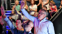 Prime Minister Scott Morrison and wife Jenny sing during an Easter Sunday service at his Horizon Church at Sutherland in Sydney, Sunday, April 21, 2019.