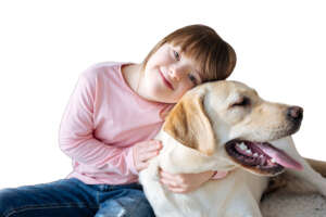 Child with down syndrome cuddling with dog