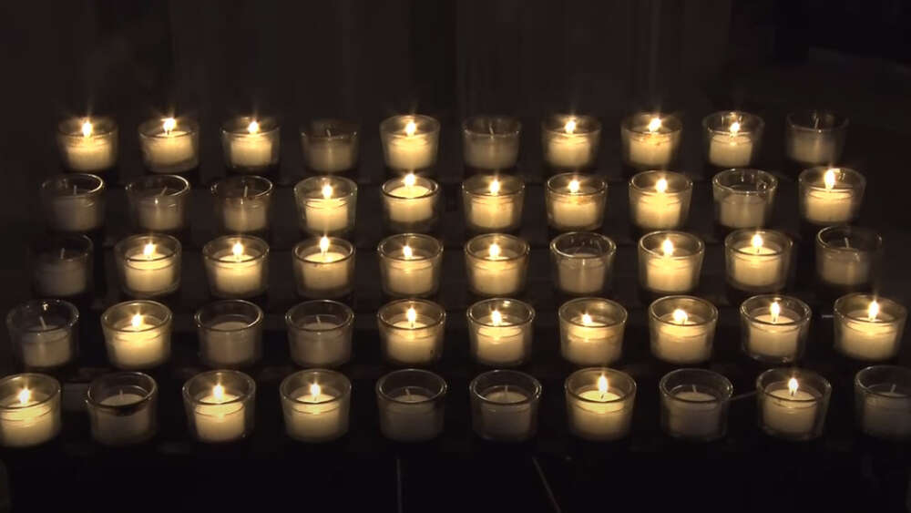 Washington Cathedral candles flicker as mourning bell tolls 500 times for 500,000 COVID deaths.