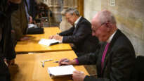 Harry Goodhew (front) and Stuart Piggin sign copies of the biography.