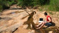 Man on laptop by desert stream